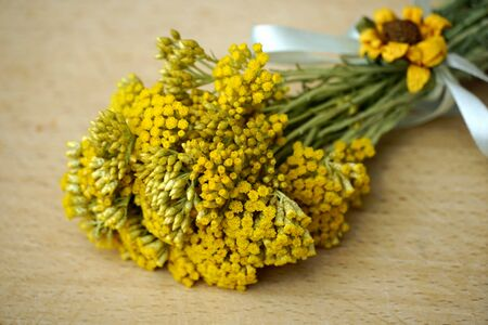 Bouquet of immortelle or everlasting flowering branches in the bouquet on the wooden background