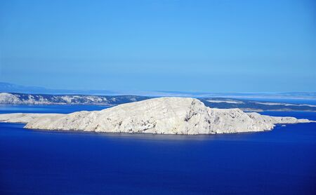 Aerial view of the big white rocky island surrounded by deep blue sea and the blue sky above lighted by sun. Scenic nature background