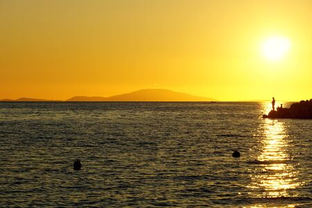 Silhouette of fisherman on the seacoast and mountain in the background of the beautiful summer sunset in yellow, beige and blue color tone