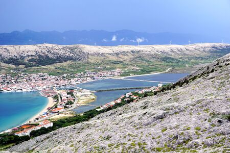 Karst landscape on the Croatian island of Pag and town Pag in the valley with salt field