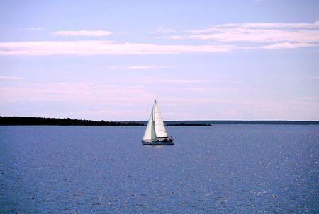 Picturesque nature background with yacht that sails calmly on the blue sea against a background of blue sky with white clouds Standard-Bild
