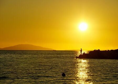 Fisherman fishing on the rocky pier in the beautiful sea sunset in yellow color tone