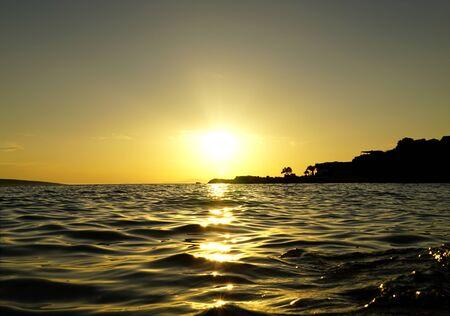 Shining sun ball above the sparkling sea water surface at sunset Standard-Bild