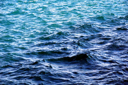 Blue background with wavy, sparkly and rippled sea surface water in blue and turquoise color tone