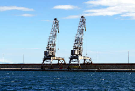 Two old, abandoned and rusty big cranes in the sea transit harbor
