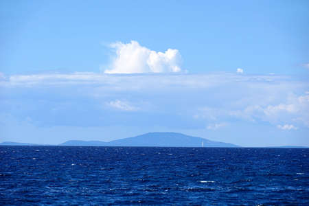 Beautiful view to sea horizon with indigo blue color tone of water and light blue sky with big white clouds