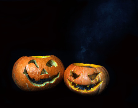 frightful: Two scary heads out of a pumpkin. The fire has already gone out. Good and evil heads. Holiday Halloween.