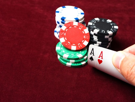 Pair of aces in a poker game. Poker chips, cards and red cloth. The concept of luck in the game.