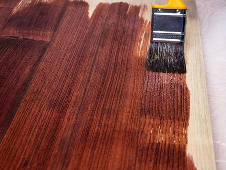 Close-up hand gebruik penseel verf duidelijk lak op hout oppervlak. Verschillende aantallen lagen en dus verschillende kleuren.