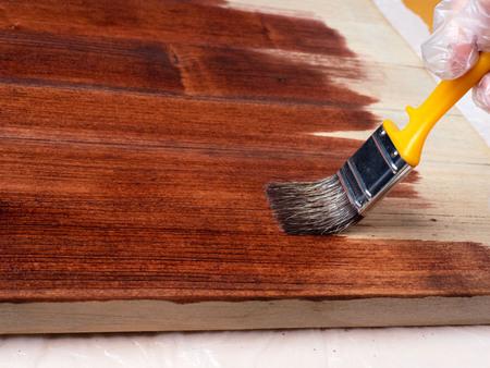 Z bliska użyj pędzla bezbarwnego lakieru na powierzchni drewna. Ręce są chronione rękawiczkami. Zdjęcie Seryjne