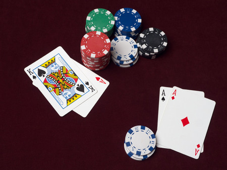 Poker chips and cards on red cloth. The chance to win back a player with aces, but his pot is too small.