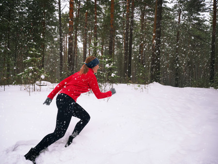Young woman fitness model running in a city park. Runner jogging in snow. Winter running exercise. Large snow is falling.