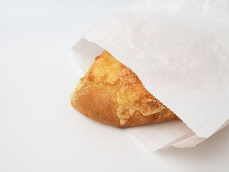 Cheese bread, packed in a paper bag, isolated on white. Banco de Imagens