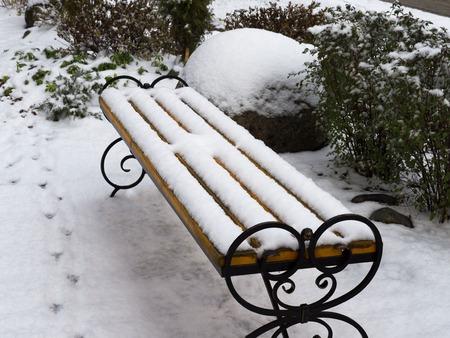 Bank in der Parkgasse bedeckt mit Schnee im frühen Winter. Vogels Spuren. Vintage-Stil. Standard-Bild