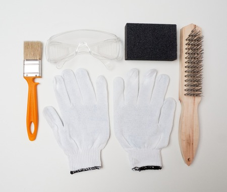Respirator, gloves, brush and glasses lying on the white surface. A set of tools for safe work with wood.