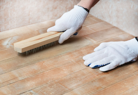 Female's hands in white protective gloves handle the wooden surface with a metal brush. Isolating the texture of a wooden surface.