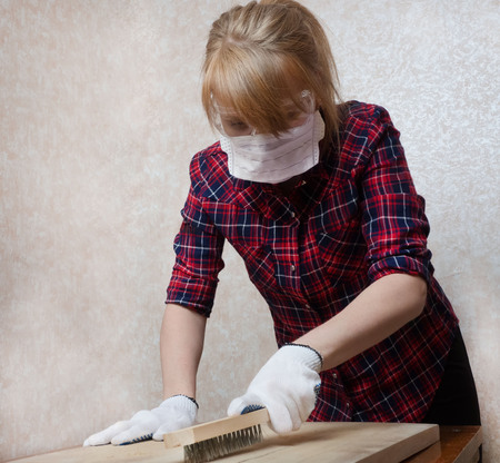 A girl in protective glasses, a mask and gloves is working on the surface of a wooden board. Safety at work is important.