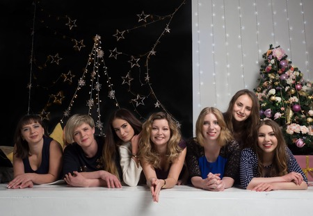 The company of pretty girls meets the new year. Lie together on the background of a Christmas tree and garlands.