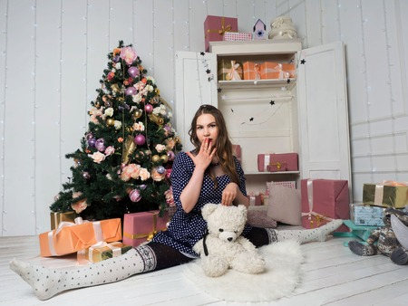 Beautiful young girl sitting on a splinter among gifts and a Christmas tree. Stockings with snowflakes and a sexy look.