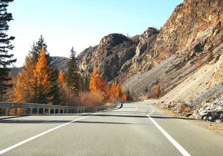 Asphalt road in autumn at sunrise. Landscape with beautiful empty mountain road with a perfect asphalt, high rocks, trees and sunny sky. Travel background. Highway at mountains. Speed.