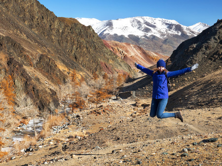 The young girl happy jump in mountains with exciting view. Autumn mountain landscape. Banco de Imagens