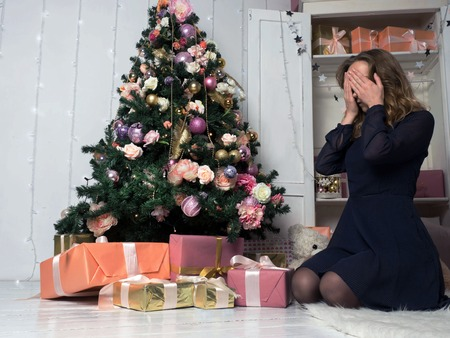 A young girl in front of a sitting in front of a Christmas tree, eyes closed with her hands in anticipation of choosing a gift. The spirit of Christmas.