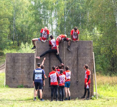 NOVOSIBIRSK, RUSSIA - 2 SEPTEMBER 2017. Young people pass the obstacle course. Mud race runners. Teamwork. Редакционное