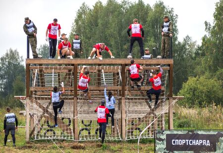 NOVOSIBIRSK, RUSSIA - 2 SEPTEMBER 2017. Young people pass the obstacle course. Mud race runners.