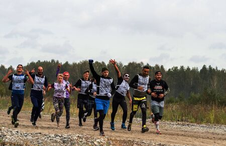 NOVOSIBIRSK, RUSSIA - 2 SEPTEMBER 2017. Young people pass the obstacle course. Mud race runners. Run to the next test point. Teamwork.