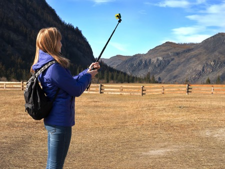 Young blonde woman backpacker taking photo with action camera on mountain peak. Autumn nature. Banco de Imagens