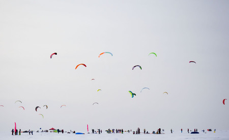 Silhouette of athletes and sailboat kitesurfing against a cloudy sky background. Beautiful colored sails.