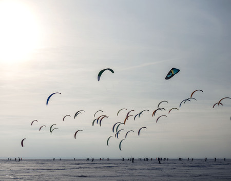 Silhouette of athletes and sailboat kitesurfing against a cloudy sky background. Banco de Imagens
