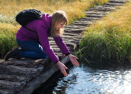 Young woman drinking water from outdoor stream with her hands. A natural source of health.