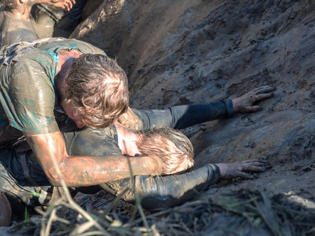 Young mans pass the obstacle course. Mud race runners. All in the mud. No strength to climb the mountain. Banco de Imagens