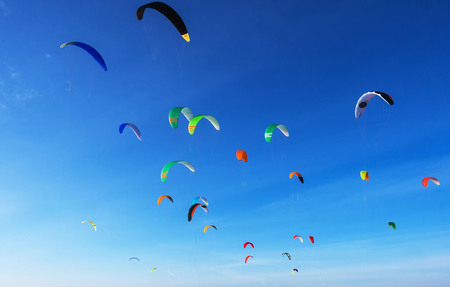 Colourful kites in flight airborne against a blue sky. Kite surfing on the sea. Banco de Imagens - 103749356