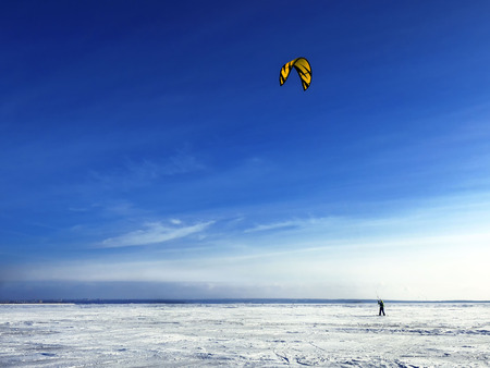 Kitesurfing in the winter. Skating on the ice in the wind. Beautiful colored sails. A single rider, solitude with the elements.