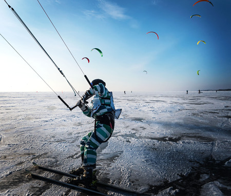 Kitesurfing in the winter. Skating on the ice in the wind. Beautiful colored sails. Banco de Imagens - 103749384