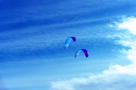Colorful kites flying in a blue sky with air clouds. Banco de Imagens