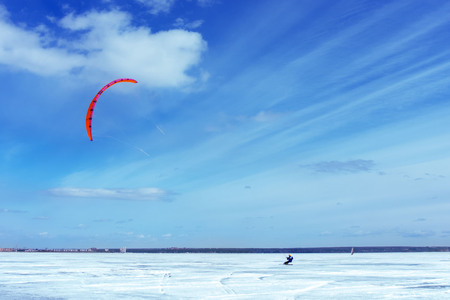 Kitesurfing in the winter. Skating on the ice in the wind. Beautiful colored sails.