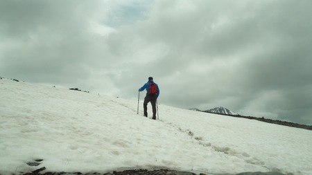 Man trekking in snow covered mountain landscape using snowshoes and trekking poles. Winter outdoor activity in the mountains.