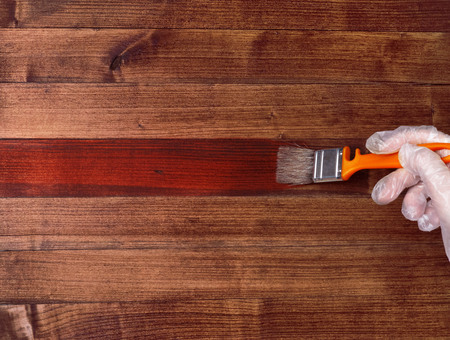 Paint brush on a wooden table. House renovation. Varnishing natural wood with a smear of the paint brush.
