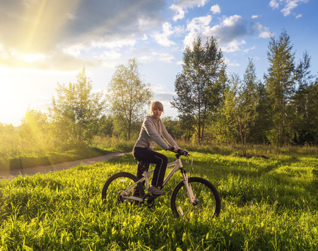 Girl on a bicycle in the sunset. The concept of freedom and travel.