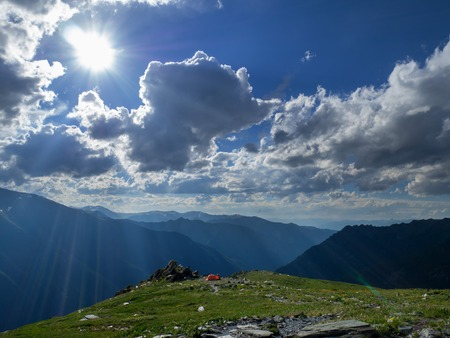 Tourist tent in mountains in the summer. Majestic light and rays in the mountains landscape.