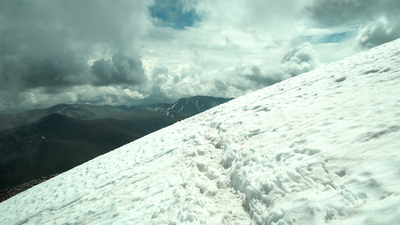 Snowy path to the top of the mountain. Dramatic storm clouds.