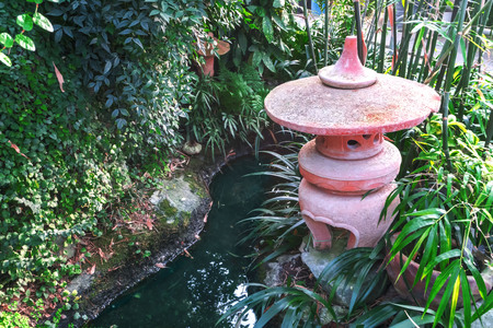 Landscaping in the Japanese style. An artificial pond, shrubs and clay sculpture. Banco de Imagens - 109111406