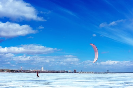 Snowboarder with a kite on the sea in the winter. The concept of winter sports. 스톡 콘텐츠