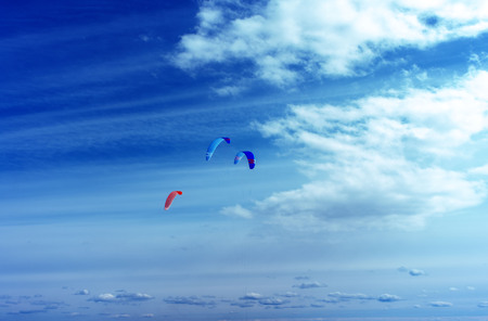Colorful kites flying in a blue sky with air clouds. Kite surfing on the sea.