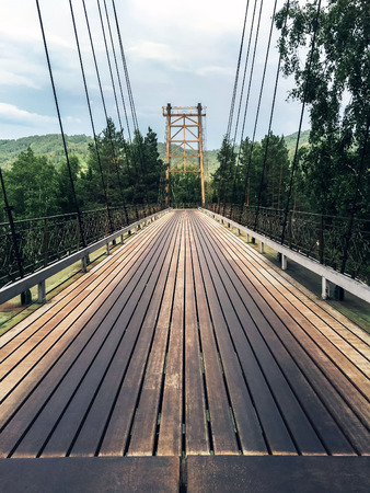 A large long bridge with a wooden road cover. Dark traces of use.