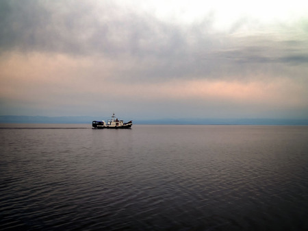 Cargo ship sailing in late afternoon with with storm clouds. Dangerous weather.