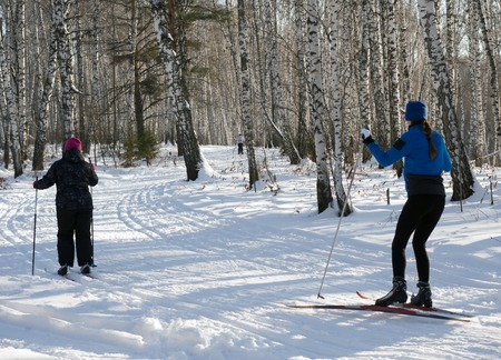 Family skiing in the forest on a sunny day. A healthy lifestyle and family values. Stock Photo